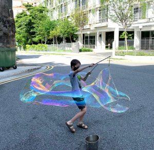 boy making giant bubbles